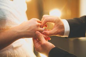 A groom putting the ring on the bride