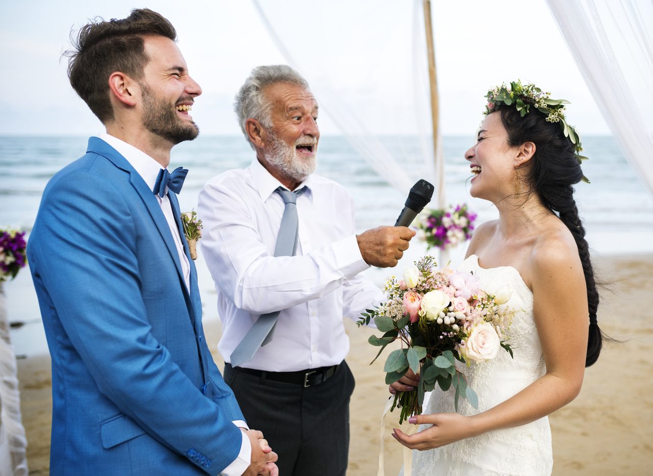 A young couple getting married laughing with their officiator