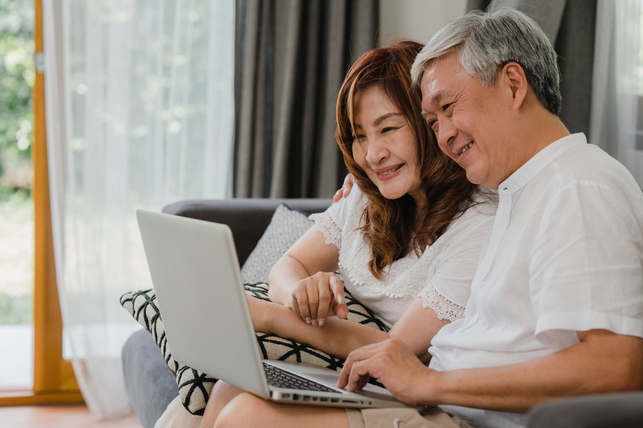 A senior asian couple is looking at a laptop