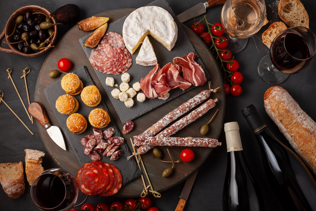 Charcuterie board of different types of meats, cheese, and pasta