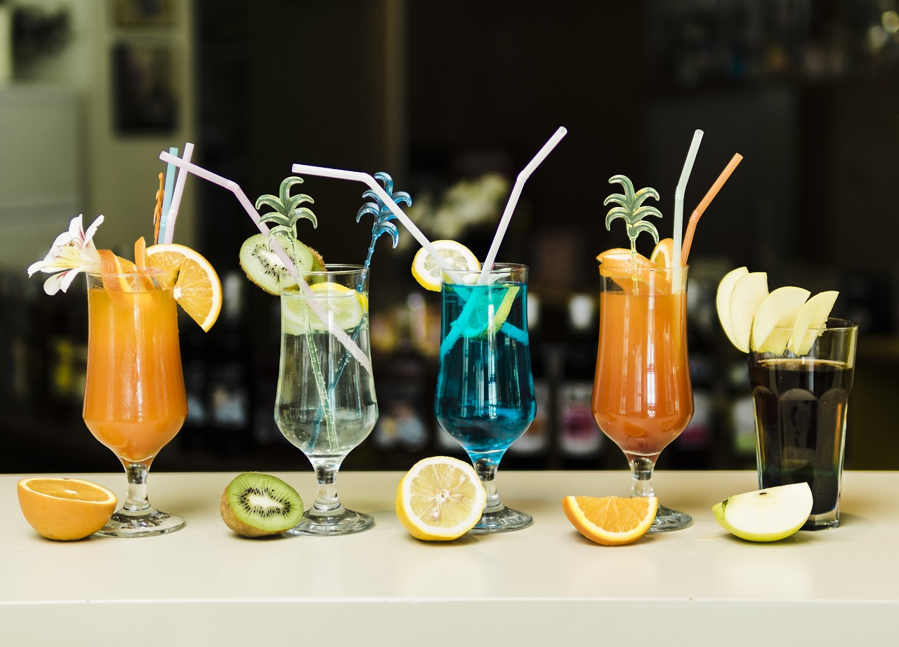 Five different types of cocktails with its respective fruit in front of it