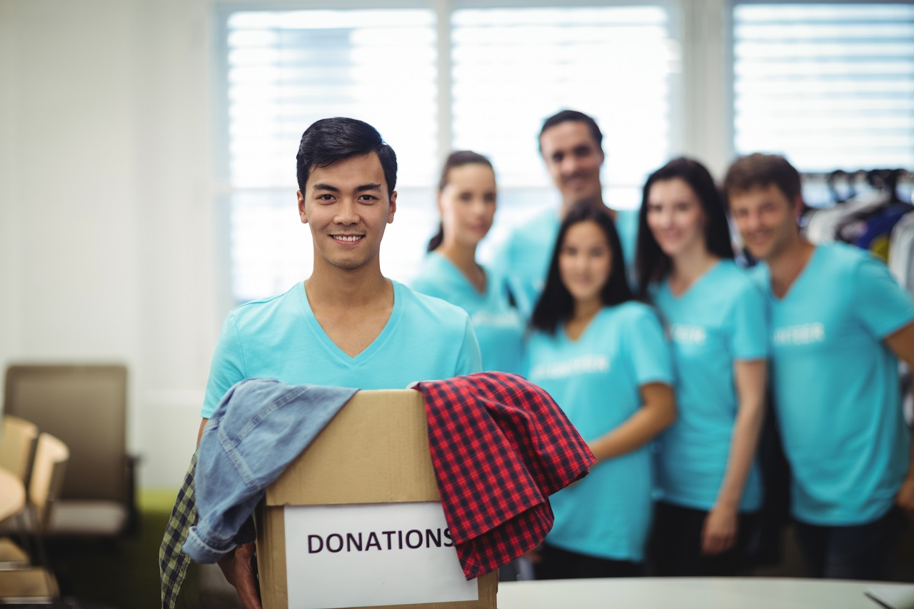 A young man holding a box of donations with his volunteer friends in the background