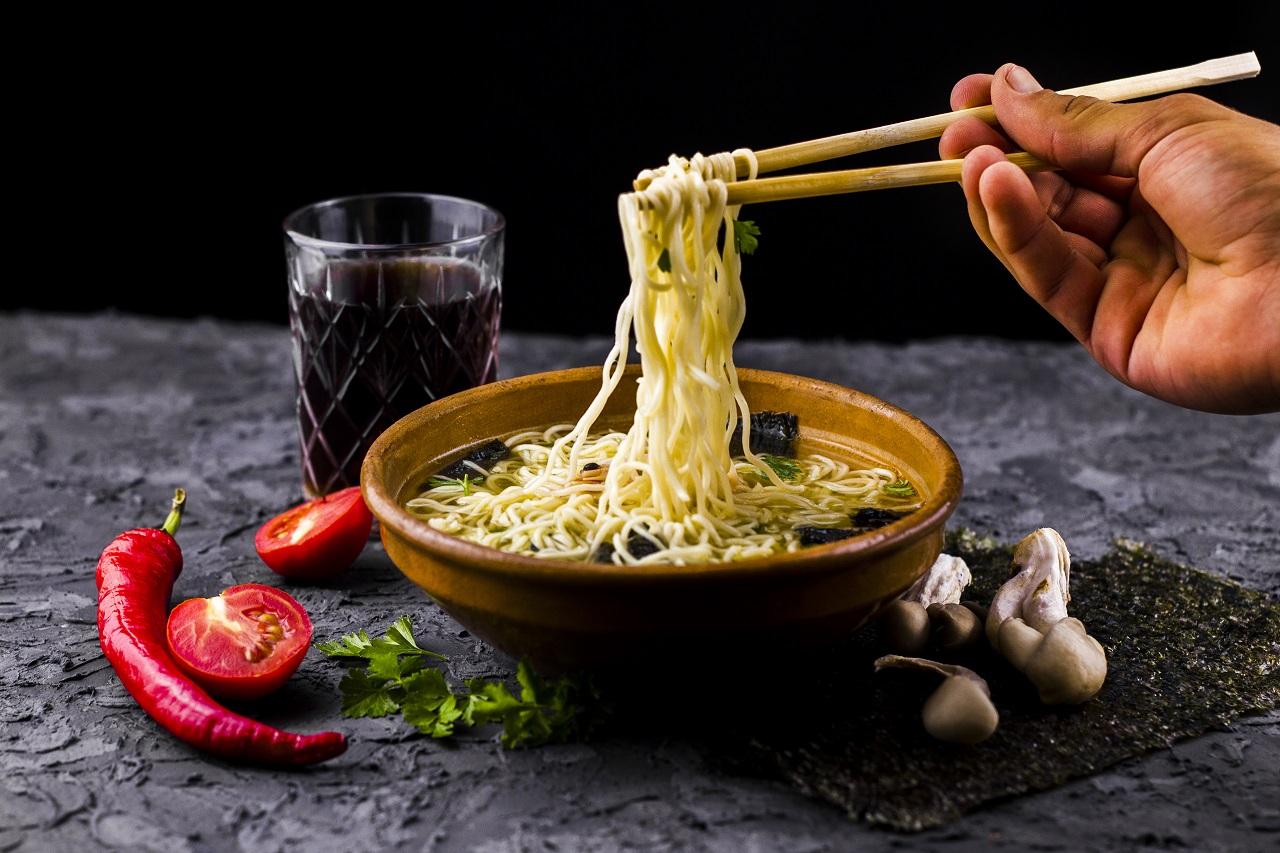 Chopsticks holding up long pieces of noodles