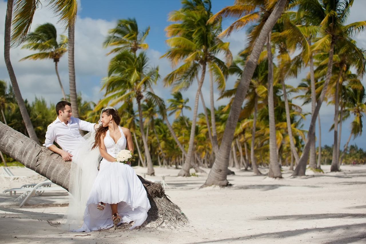 A bride and groom having a wedding photoshoot at the beach