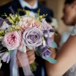 A bride and groom holding up the flower bouquet
