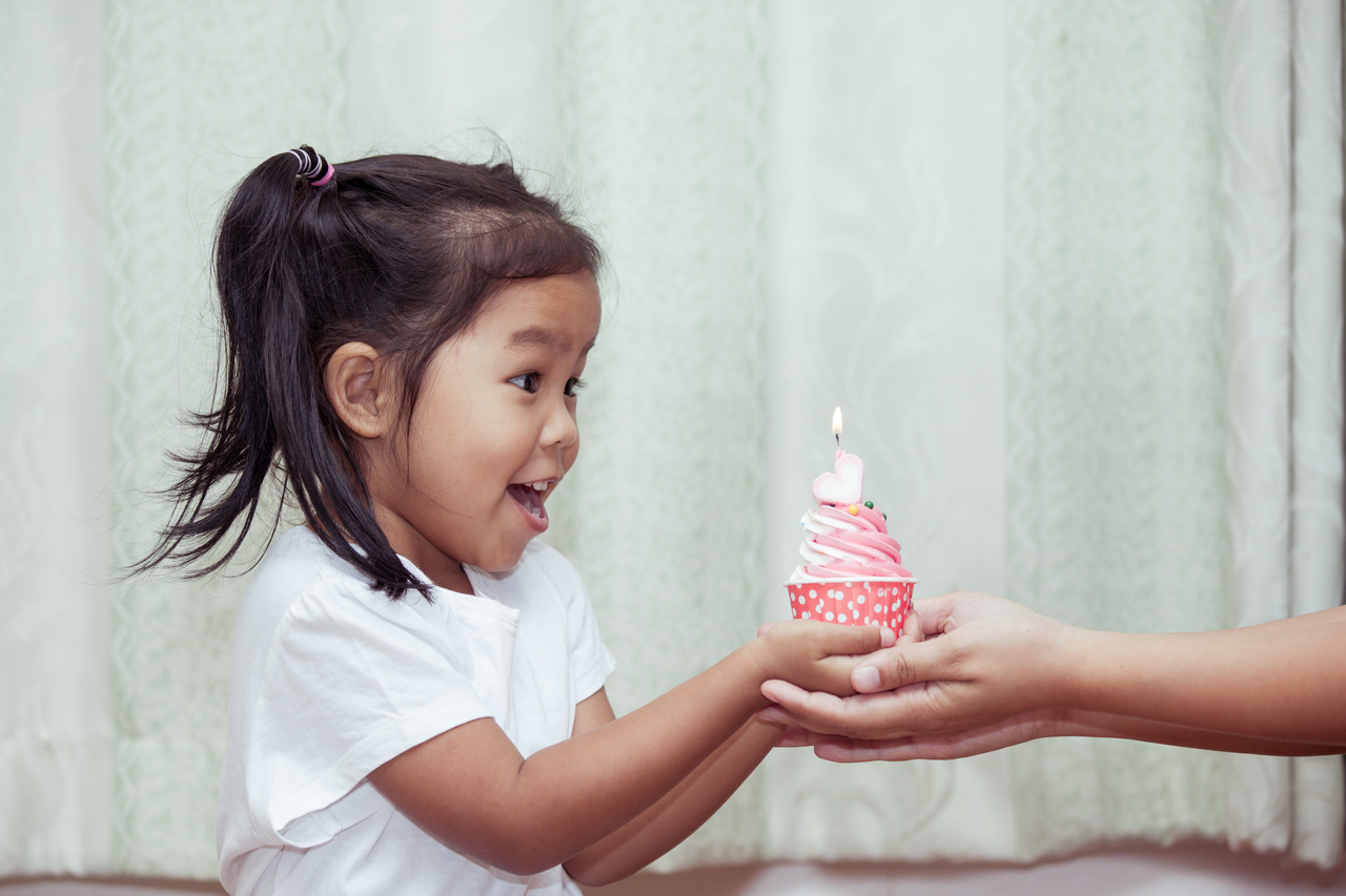 An little girl celebrating her birthday with a cupcake