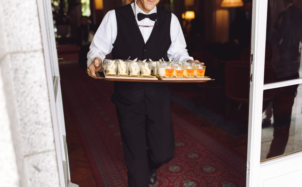 A professional caterer carrying a tray of food