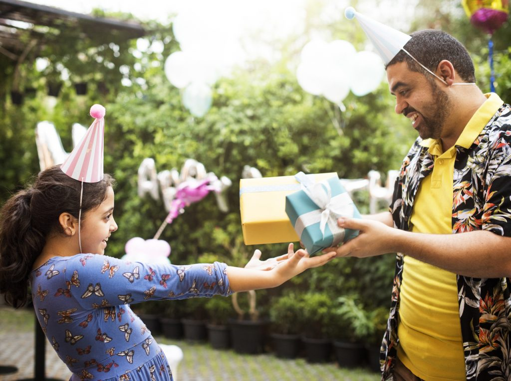 A man giving his daughter a gift for her birthday