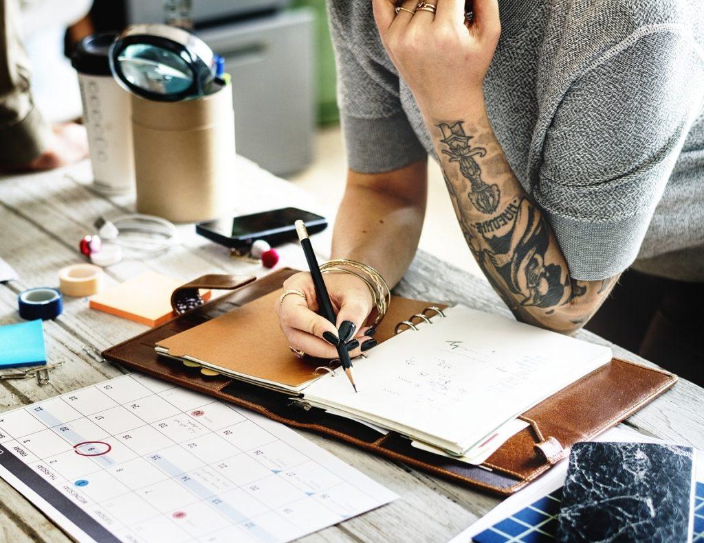Tattooed woman planning