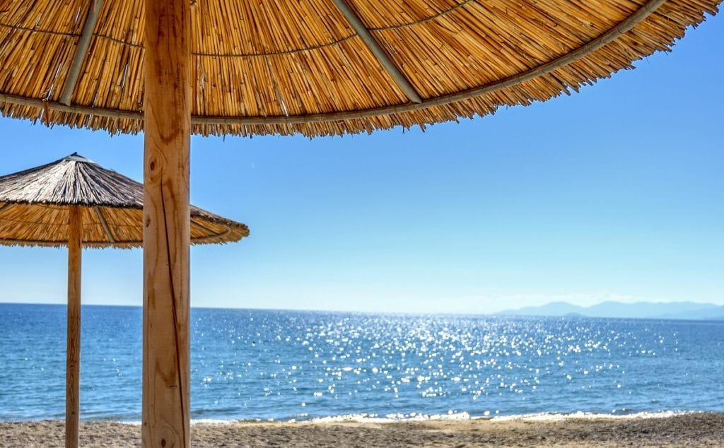 Reed umbrellas and sun beds at the empty beach in Asprovalta